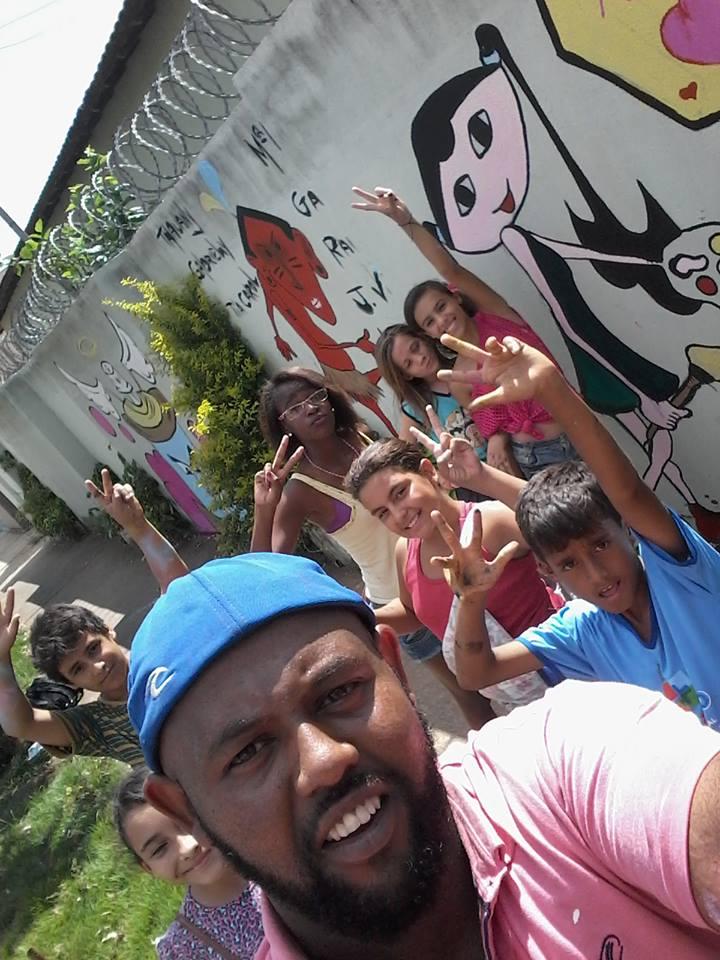 O professor de artes Silas Cândido e as crianças trabalhando as pinturas no muro do Caps